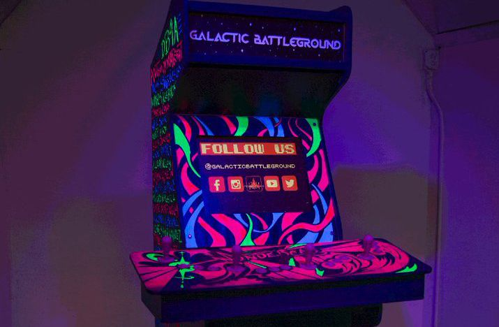 a video game cabinet covered in sick black light designs.